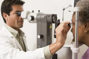 living in well being image doctor checking the eye of a  patient for detecting astigmatism