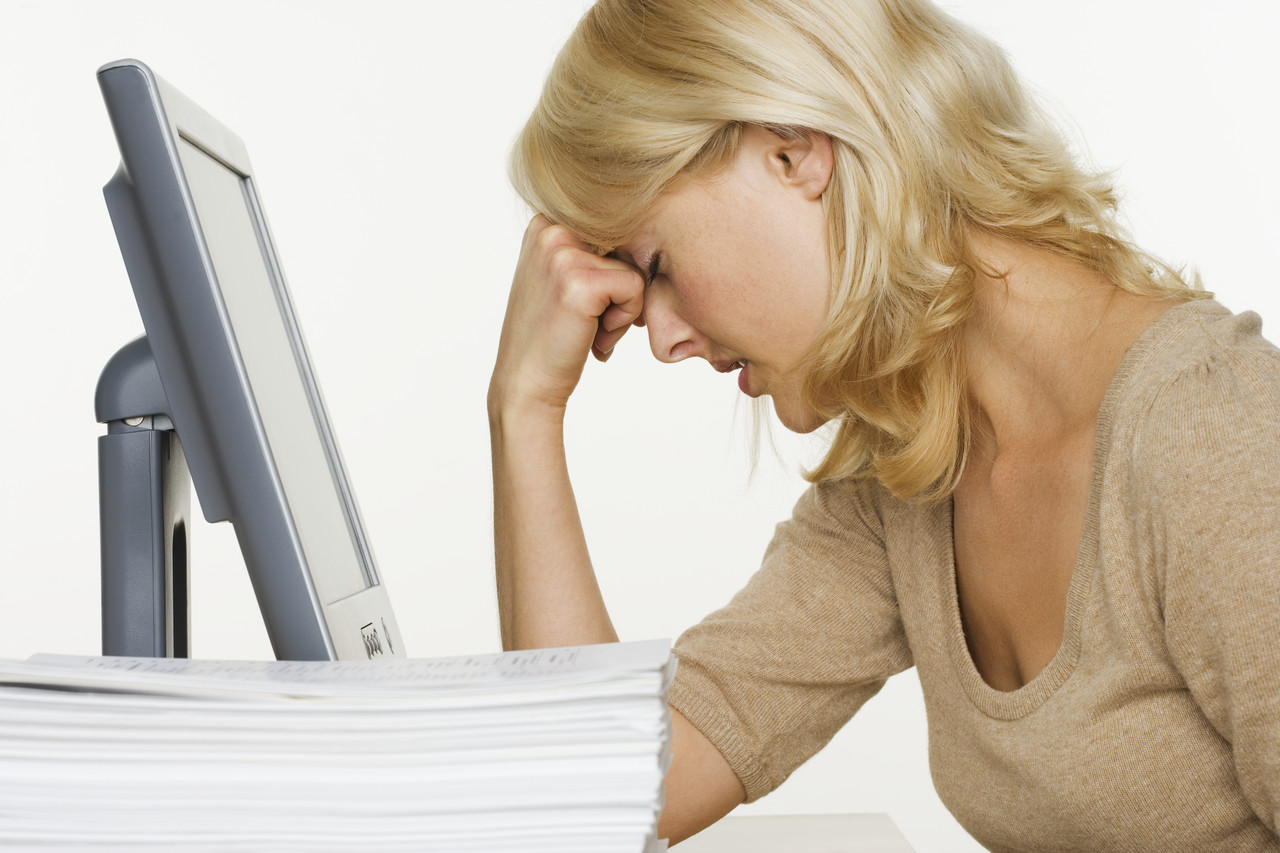 living in well being Frustrated Woman at Computer With Stack of Paper